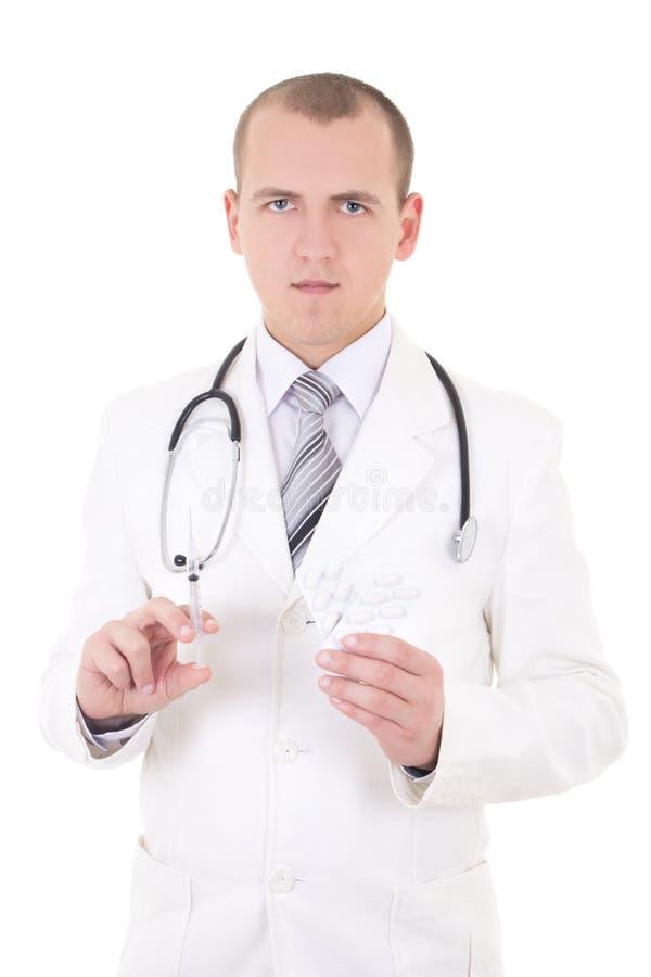 Молодой доктор с шприцем и пакетом пилюлек изолированных на белизне стоковые изображения