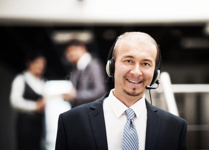 Молодой оператор обслуживания клиента говоря на шлемофоне, усмехаясь стоковое фото rf