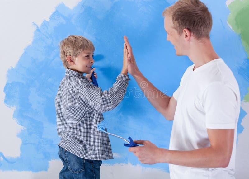 Молодой отец давая максимум 5 к его маленькому сыну стоковая фотография