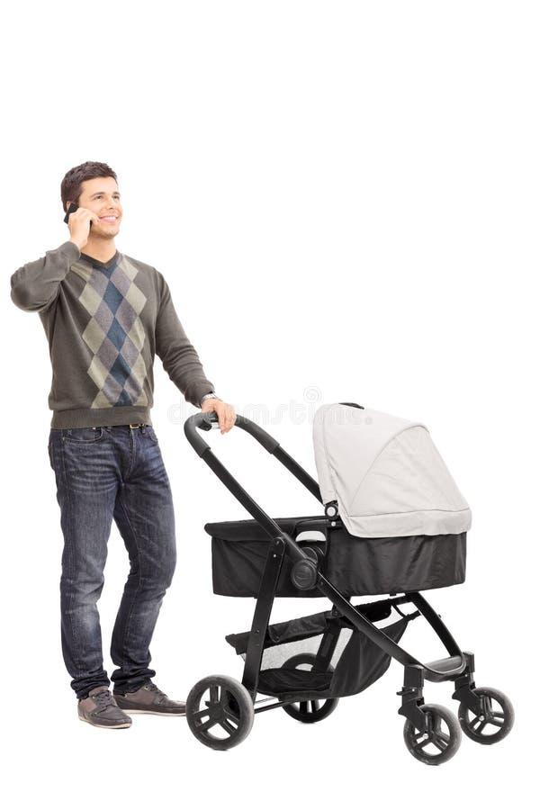 Молодой отец говоря на телефоне и нажимая детскую сидячую коляску стоковое фото rf
