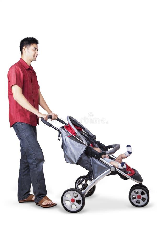 Молодой отец нажимая детскую дорожную коляску стоковая фотография