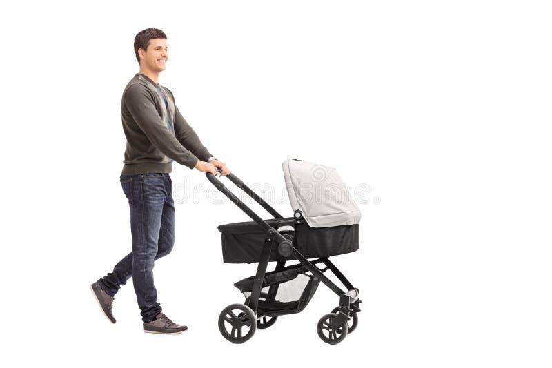 Молодой отец нажимая детскую сидячую коляску стоковые фотографии rf