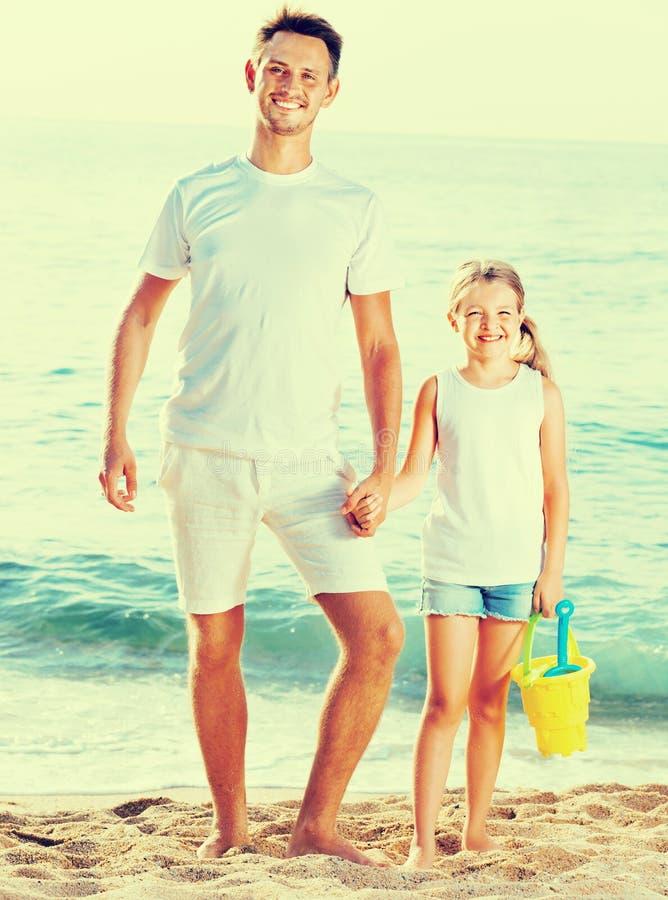 Молодой папа при девушка стоя на пляже с игрушками стоковое фото rf