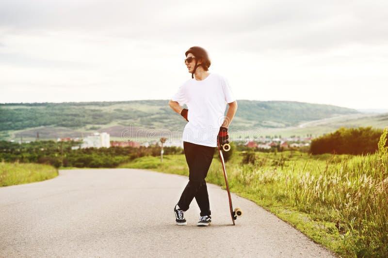 Молодой парень - конькобежец стоя в ожидании гонку на проселочной дороге стоковое изображение