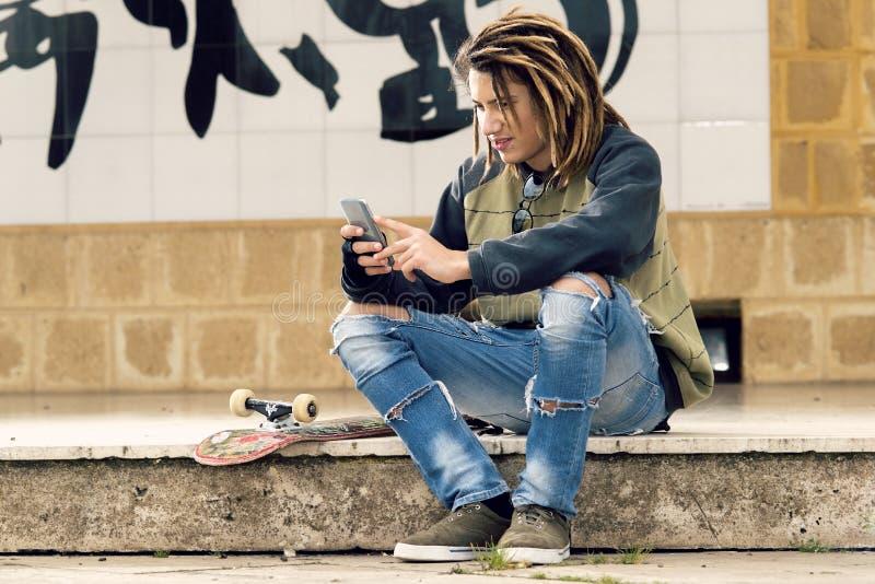 Молодой парень моды с smartphone стоковое изображение