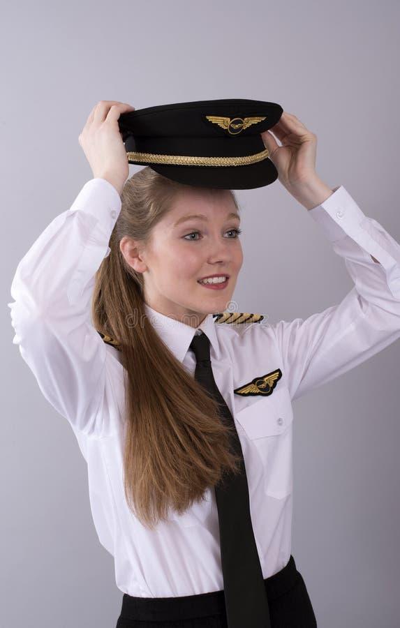 Молодой пилот с длинной коричневой шляпой волос и формы стоковые изображения rf