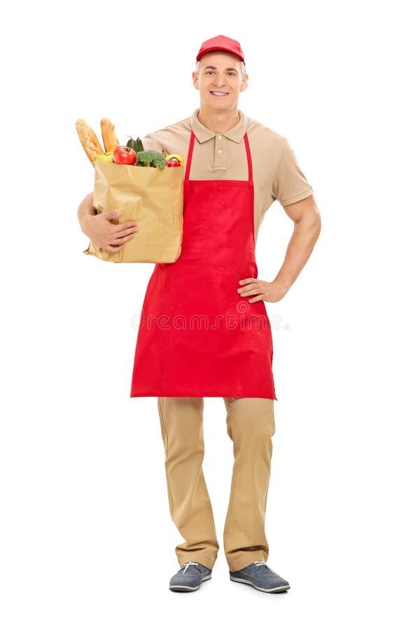 Молодой поставщик рынка держа сумку полный бакалей стоковое изображение