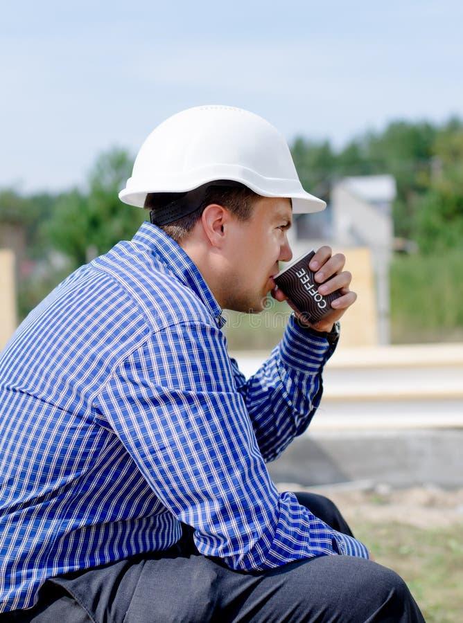Молодой построитель принимая его перерыв на чашку кофе стоковые фотографии rf