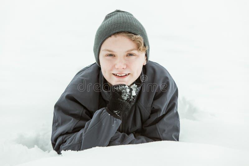 Молодой подросток лежа в снеге на зимний день стоковая фотография