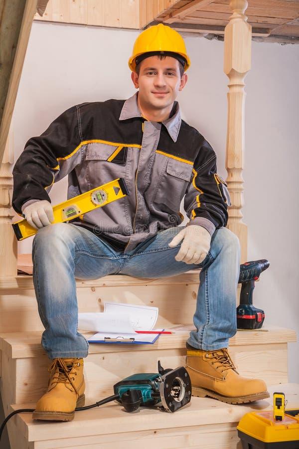 Молодой подрядчик сидя на деревянной лестнице держа constructionh стоковое изображение rf