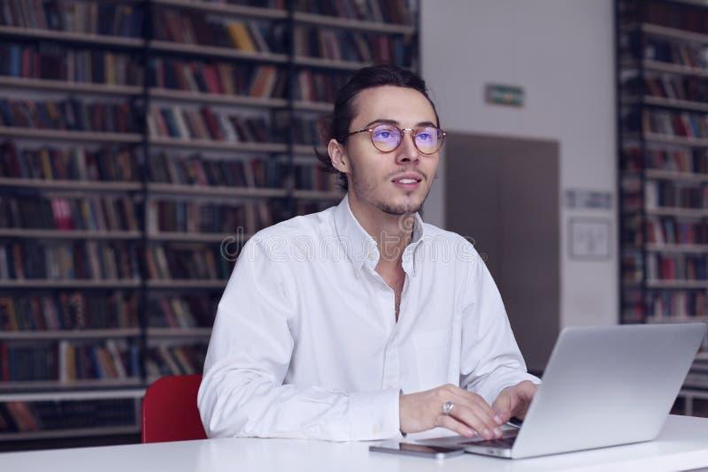 Молодой предприниматель, студент университета работая на компьтер-книжке с книгой на научном тезисе в библиотеке стоковые изображения rf