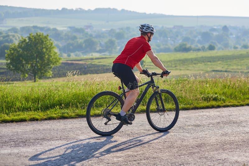 Молодой привлекательный горный велосипед катания велосипедиста на проселочной дороге стоковые изображения rf