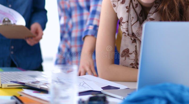 Молодой привлекательный женский модельер работая на столе офиса, рисуя пока говорящ на черни стоковые изображения