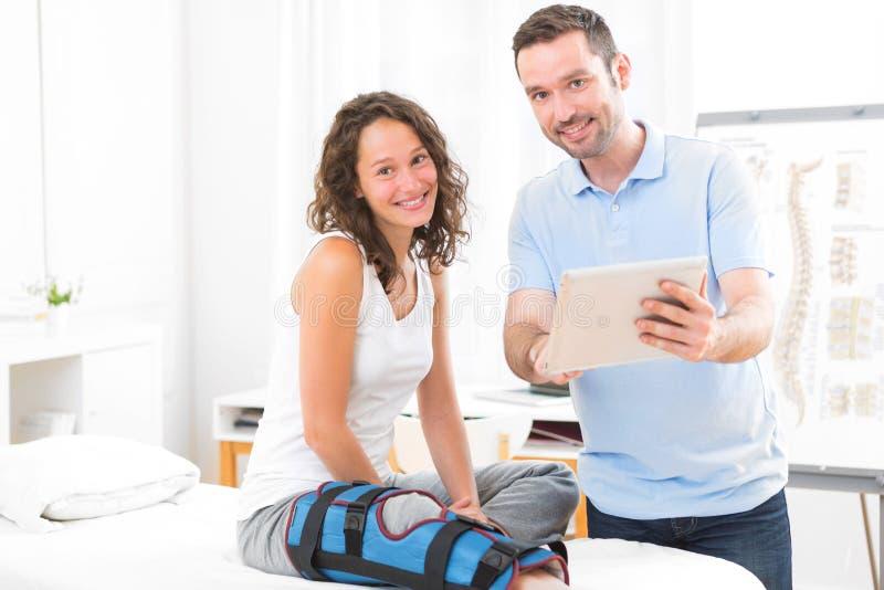 Молодой привлекательный физиотерапевт используя таблетку с пациентом стоковое фото