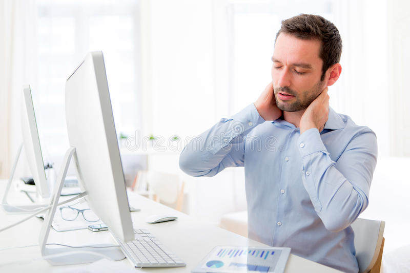 Молодой привлекательный человек получил боль шеи на офисе стоковое фото rf