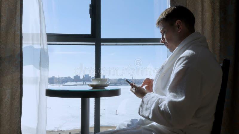 Молодой, привлекательный человек сидя на таблице чаем окна выпивая, кофе и писать сообщение SMS на черни стоковая фотография rf