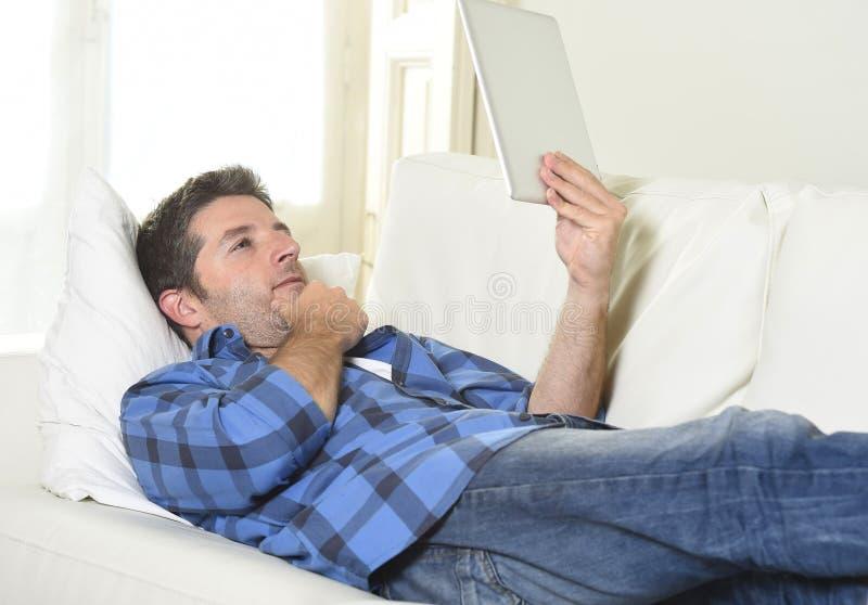 Молодой привлекательный человек 30s используя цифровую пусковую площадку таблетки лежа на сети кресла дома смотря ослабленный стоковая фотография rf