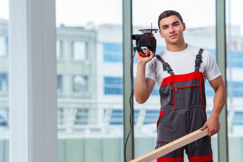 Молодой плотник работая на строительной площадке стоковое фото