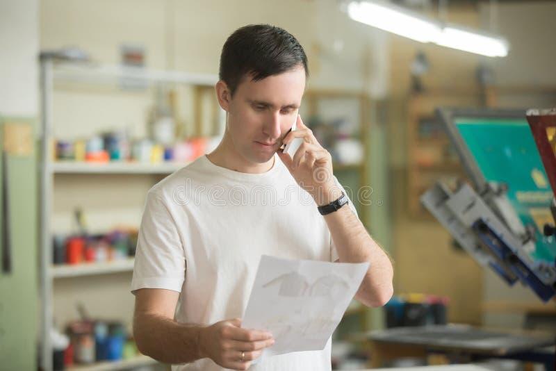 Молодой работник говоря на телефоне стоковые изображения rf