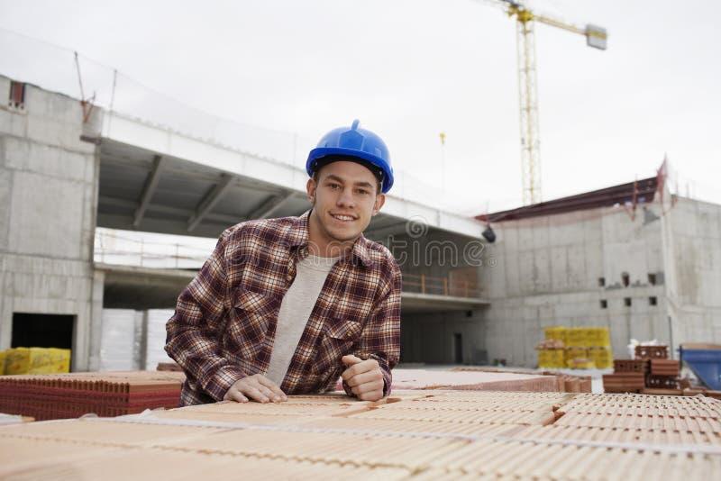 Молодой рабочий-строитель на строительной площадке стоковые изображения rf