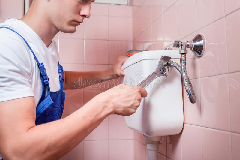 Молодой разнорабочий исправляя туалет стоковые фотографии rf
