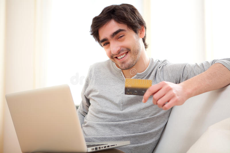 Молодой расслабленный оплачивать человека онлайн с кредитной карточкой в софе стоковые фото