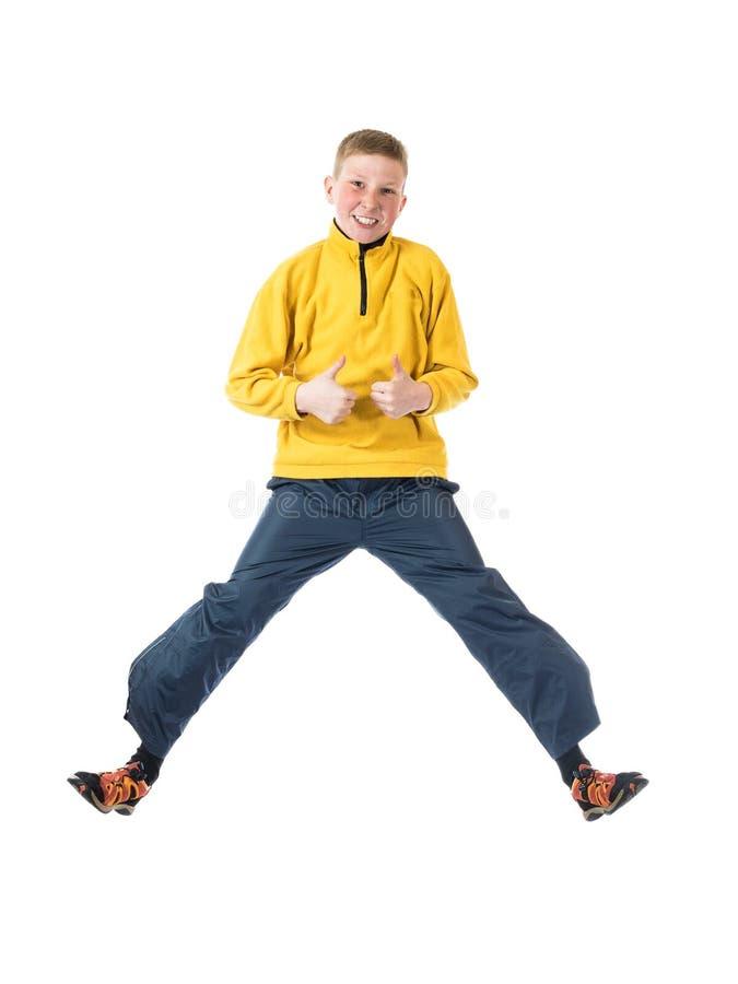 Молодой рыжеволосый мальчик в мальчике желтой куртки скача при руки обхваченные в кулаке и поднятые его большому пальцу руки ввер стоковая фотография