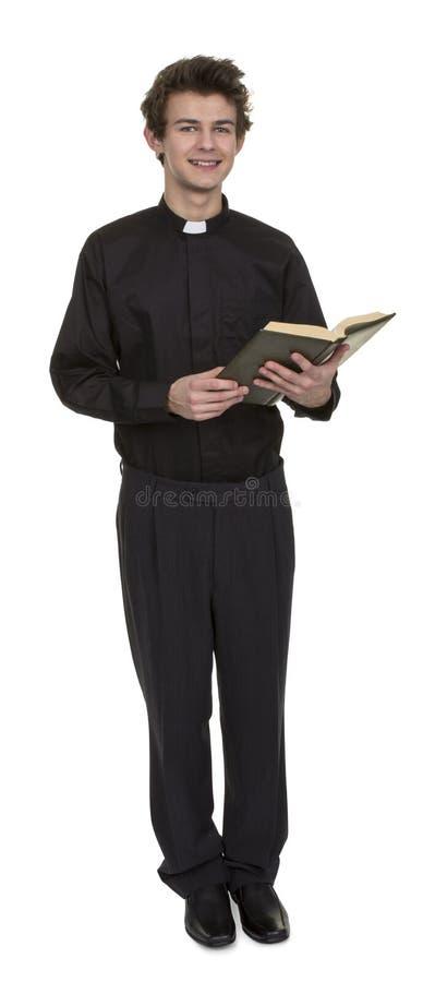 Молодой священник держа библию стоковое изображение rf