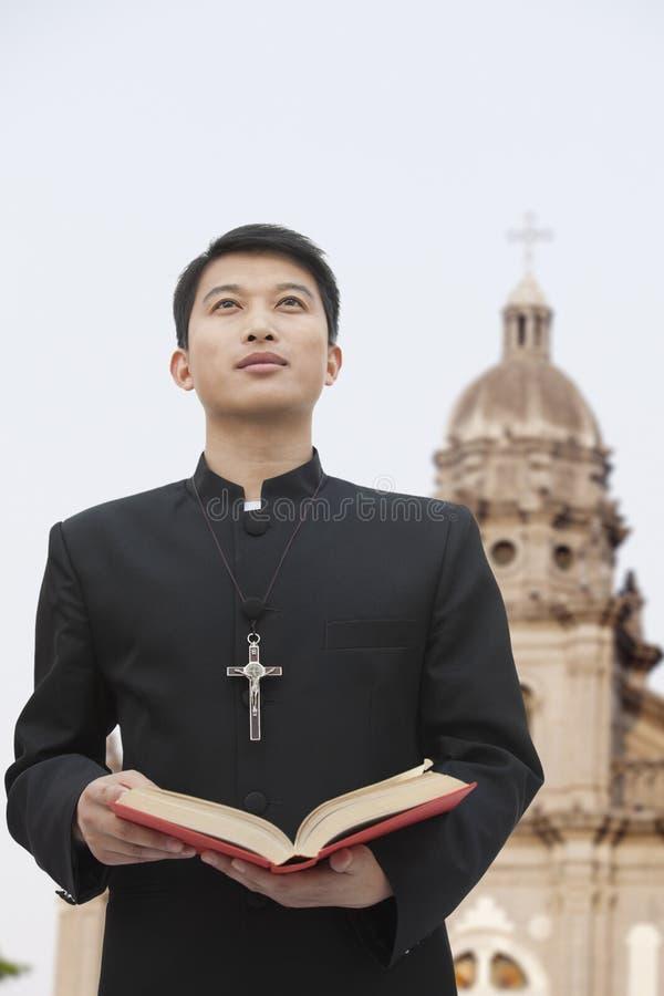 Молодой священник смотря к небу перед церковью, держа библию стоковые фотографии rf