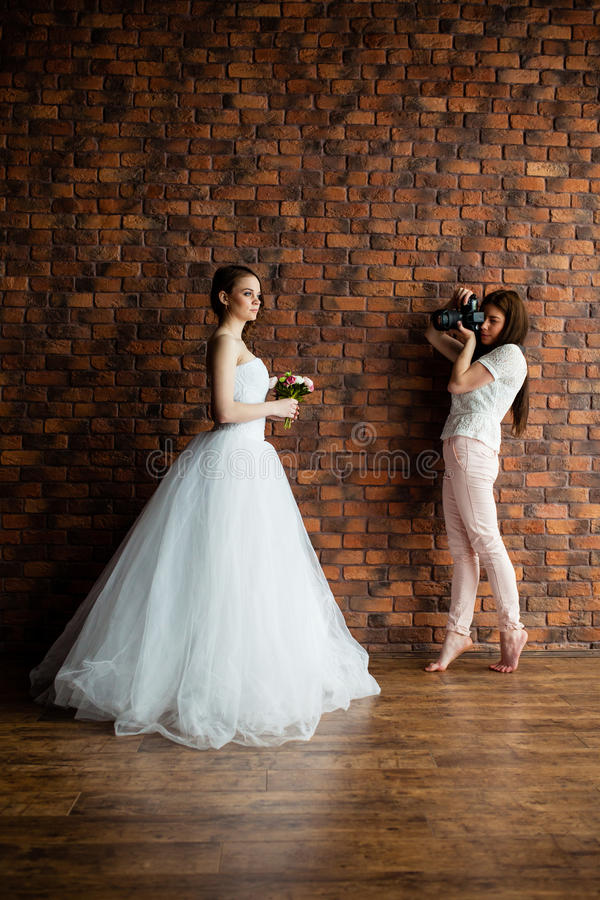Молодой сексуальный фотограф принимает изображениям невесту в студии стоковые изображения rf