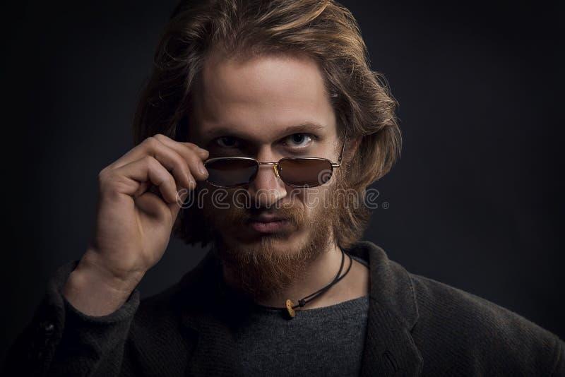 Молодой серьезный человек с бородой и усик рассматривая его солнечные очки стоковое фото