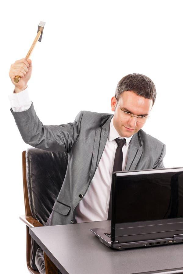 Молодой сердитый бизнесмен при молоток ломая компьтер-книжку стоковое изображение rf