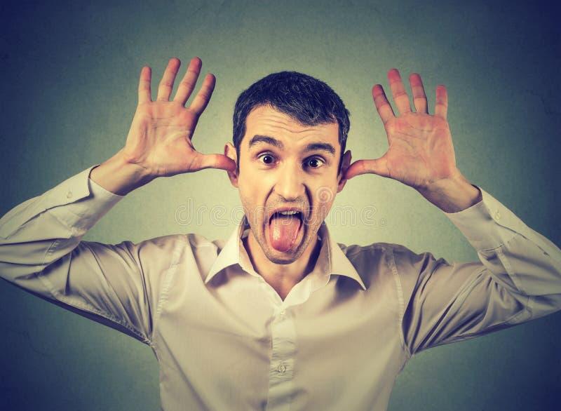 Молодой сердитый человек, вставляя вне язык на вас, жест камеры стоковые изображения