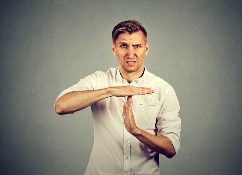 Молодой сердитый человек показывая жест рукой времени вне стоковое изображение rf