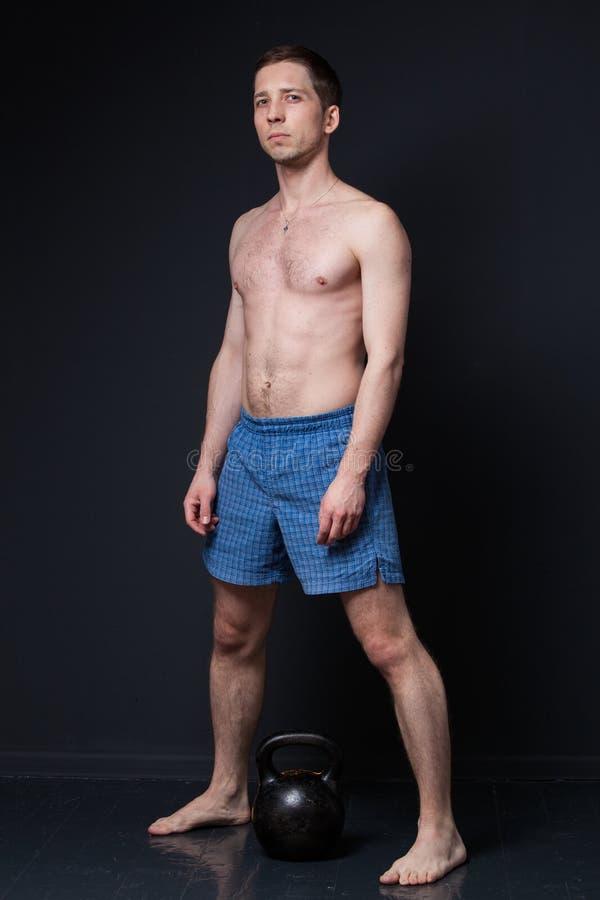 Молодой сильный человек в шортах перед тренировкой kettlebell поднимаясь стоковые фотографии rf