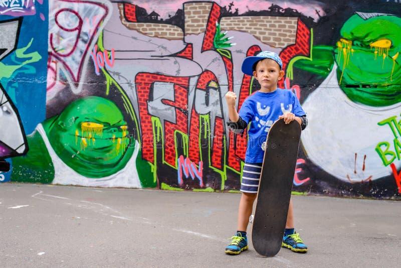 Молодой скейтбордист представляя с его доской стоковая фотография rf