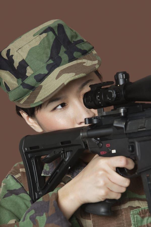 Молодой солдат морской пехот США женщины направляя штурмовую винтовку M4 над коричневой предпосылкой стоковые изображения rf