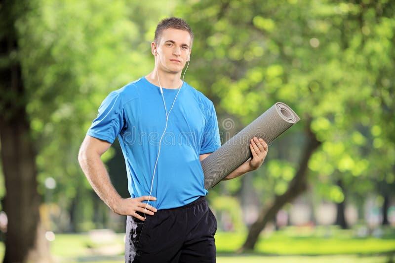Молодой спортсмен держа циновку и слушая к музыке стоковые фото