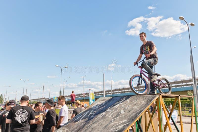 Молодой спортсмен на велосипеде BMX на пандусе готовом для того чтобы поскакать стоковое фото
