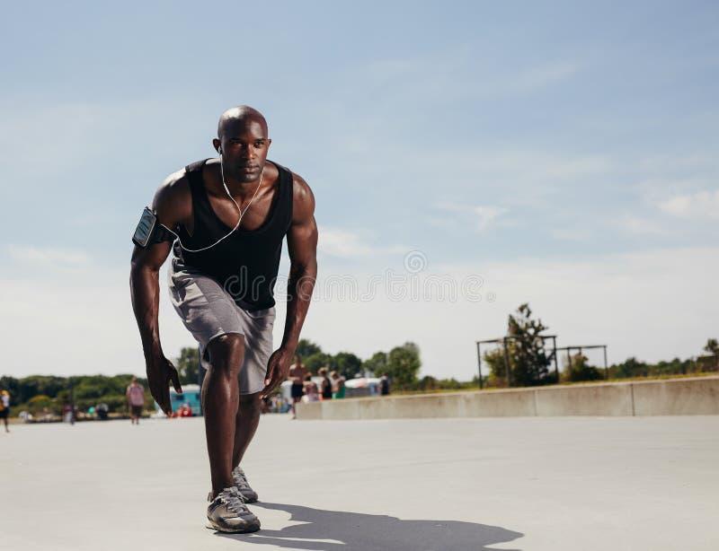 Молодой спортсмен на его метке для того чтобы начать бег стоковое изображение