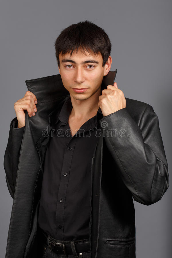 Молодой стильный человек брюнет в черной рубашке и черном кожаном пальто w стоковая фотография