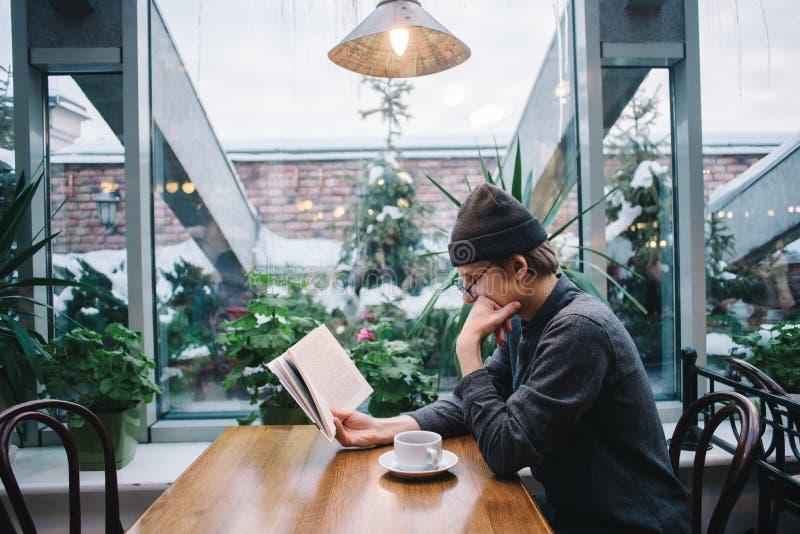 Молодой студент в крышке и рубашке читая книгу и выпивая кофе в красивом кафе с консерваторией стоковые фото