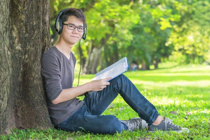 Молодой студент в парке слушая к музыке на наушниках стоковое изображение rf