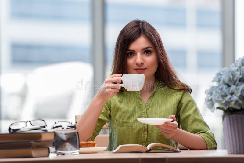 Молодой студент подготавливая для экзаменов выпивая чай стоковые изображения rf
