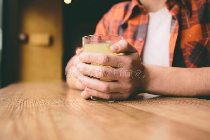 Молодой студент сидит в ресторане и пробует теплое питье чай человека выпивая на кафе стоковое фото rf