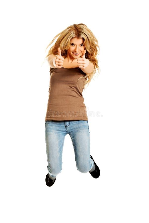 Молодой студент скача с большими пальцами руки вверх стоковое фото