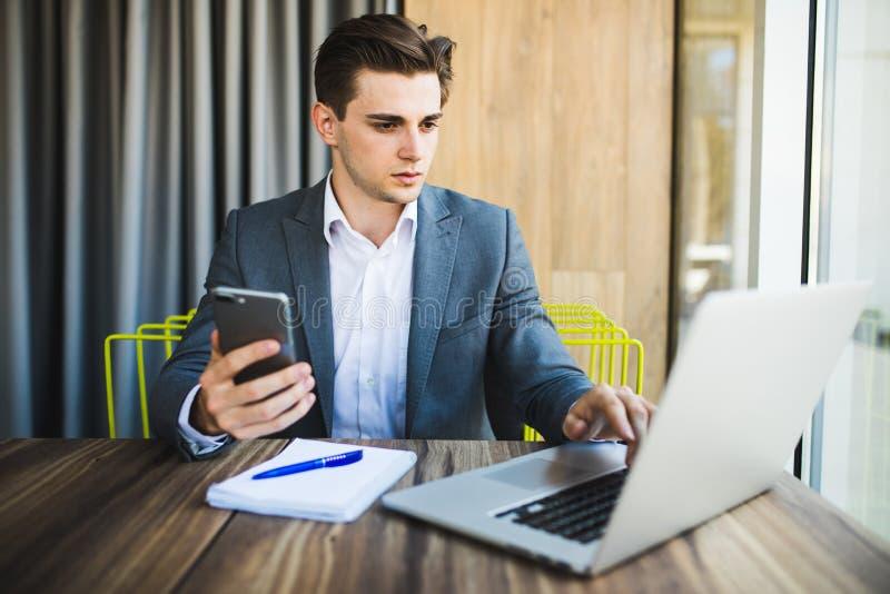 Молодой счастливый бизнесмен усмехаясь пока читающ его smartphone Портрет усмехаясь сообщения чтения бизнесмена с smartphone внут стоковое фото