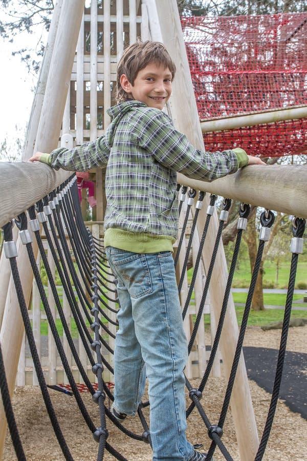 Молодой счастливый мальчик на спортивной площадке стоковые фотографии rf
