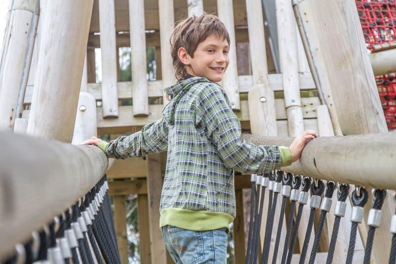 Молодой счастливый мальчик на спортивной площадке стоковое изображение