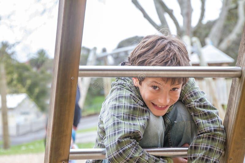 Молодой счастливый мальчик на спортивной площадке стоковое фото